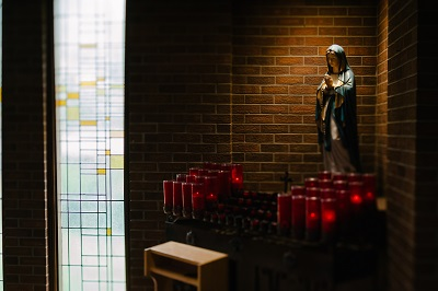 A statue of the Mother of God with candles