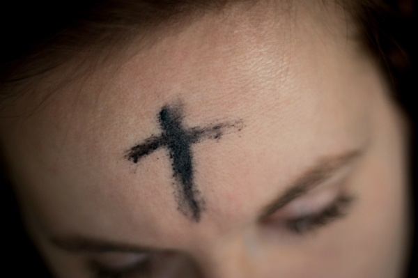 A woman's head with an ash cross carved into it